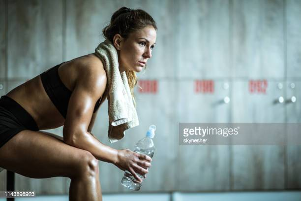 pensive athletic woman having water break in locker room. - backstage stock pictures, royalty-free photos & images