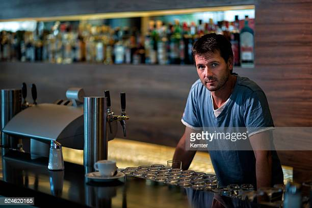 pensive barkeeper leaning at bar counter