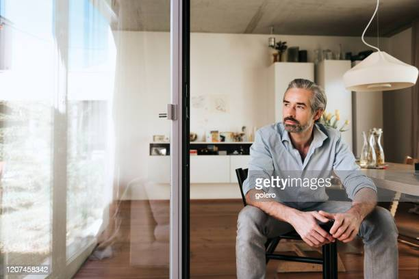 pensive bearded business man looking out of the window - finance and economy stock pictures, royalty-free photos & images