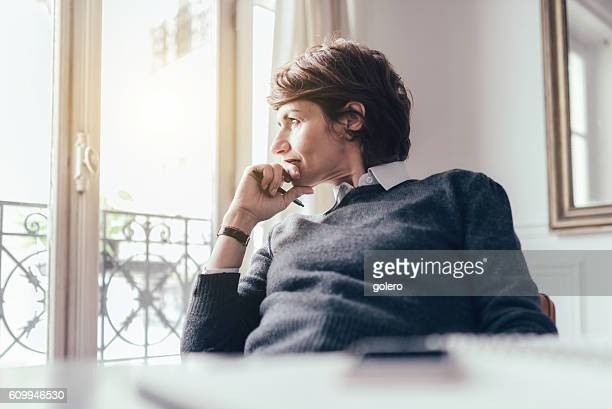 pensive beautiful french woman looking out of window