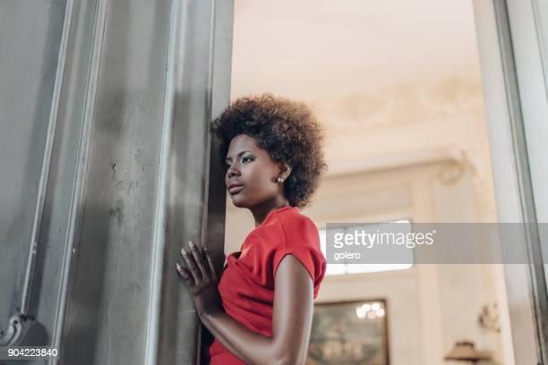 nachdenkliche schöne junge kubanische Frau an der Tür gelehnt