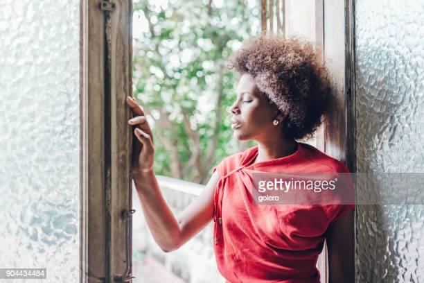 nachdenkliche schöne junge kubanische Frau dich am Fenster