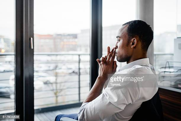 pensive black businessman looking away - looking through window stock pictures, royalty-free photos & images