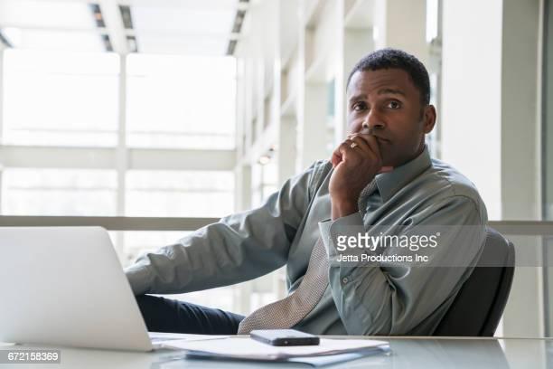 Pensive Black businessman sitting at desk