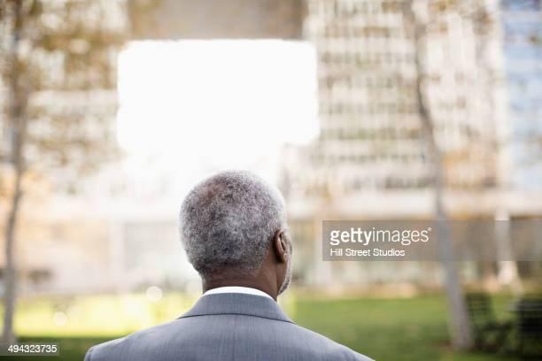 Pensive Black businessman standing outdoors