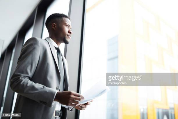 pensive black businessman with papers near window - businessman contemplation stock pictures, royalty-free photos & images