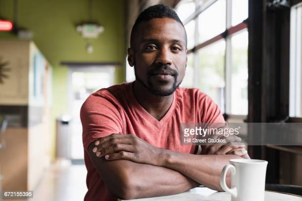 pensive black man sitting in coffee shop - grave stock pictures, royalty-free photos & images