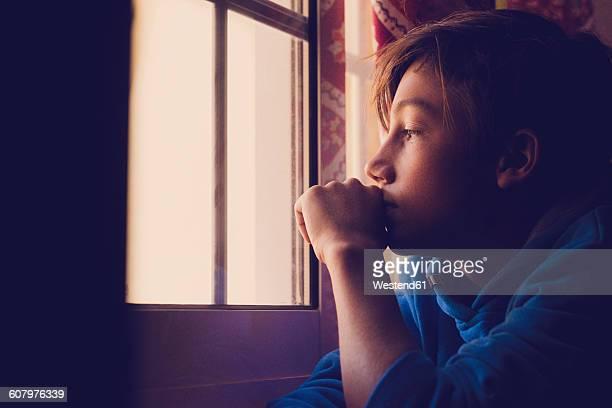 Pensive boy looking through window
