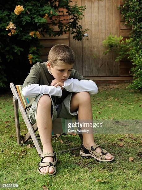 Pensive boy (8-9) sitting in garden