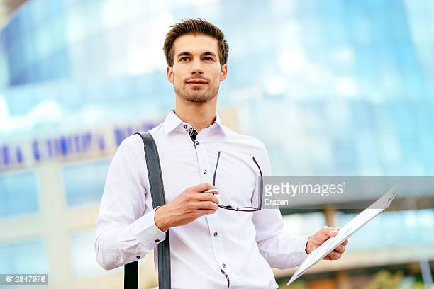 Pensive businessman holding financial report
