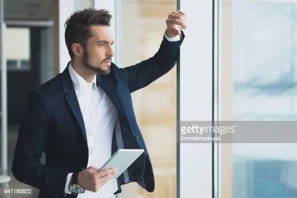 Fundersam affärsman holding tablett, funderar på nya projekt.