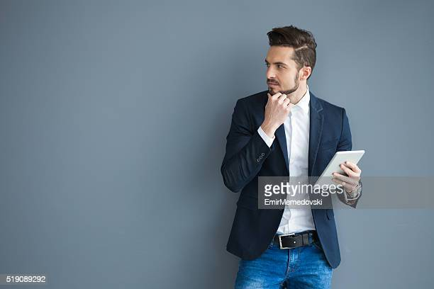 Pensive businessman holding touchpad against gray wall.