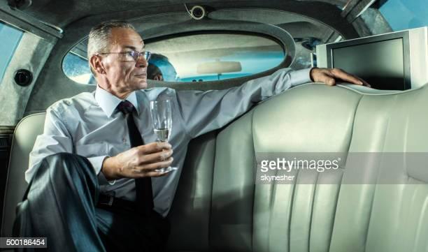 Homme d'affaires pensif dans une limousine avec un verre de champagne.