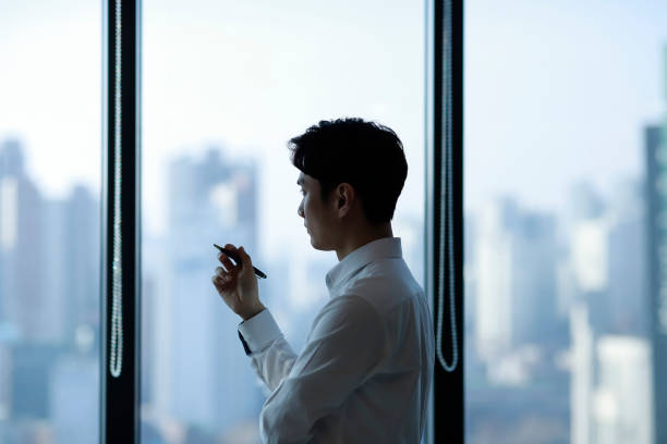 pensive businessman looking through window in office - asain office man stock pictures, royalty-free photos & images