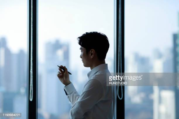 pensive businessman looking through window in office - business ストックフォトと画像