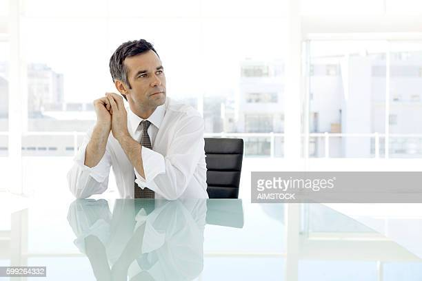 pensive businessman sitting in board room - diretor geral - fotografias e filmes do acervo
