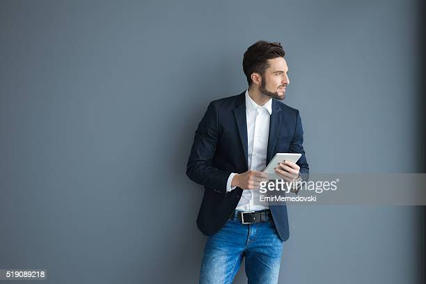 Pensive businessman with digital tablet against gray wall.