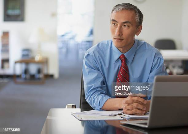Pensive businessman with hands folded