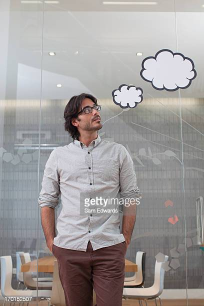 pensive businessman with thought bubbles overhead - thought bubble stock pictures, royalty-free photos & images