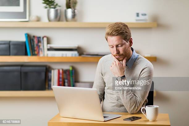 Pensive businessman working from home office using digital tablet
