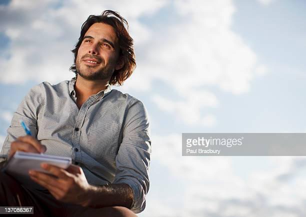 Pensif Homme d'affaires écrire dans cahier en plein air