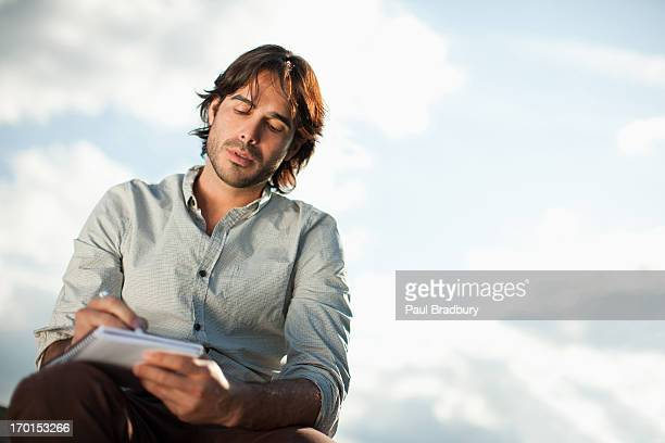 Pensive businessman writing in notebook outdoors
