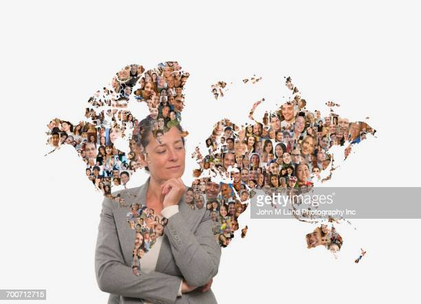 Pensive businesswoman behind global map of people