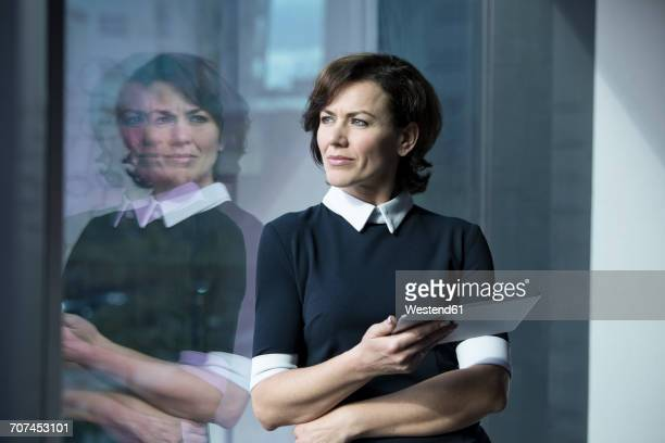 Pensive businesswoman holding tablet looking out of window