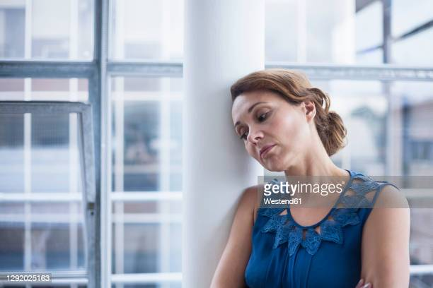 pensive businesswoman leaning on column in office - 35 39 years stock pictures, royalty-free photos & images