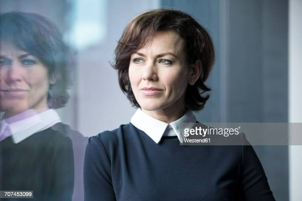 Pensive businesswoman looking out of window