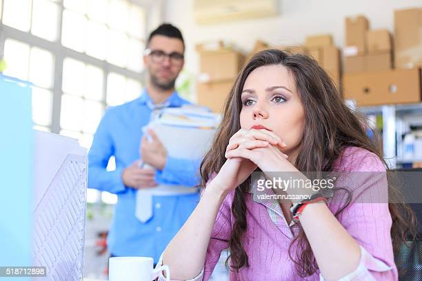 Pensive businesswoman sitting on desk at the office