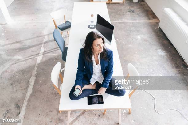 Pensive businesswoman sitting on desk in a loft with electronic devices