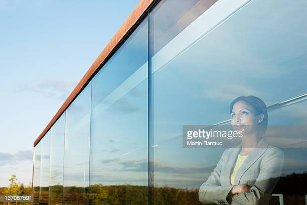 pensive businesswoman with arms crossed in office window - hope stock pictures, royalty-free photos & images