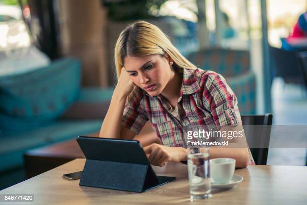 pensive businesswoman with digital tablet in a cafe - coffee drink stock pictures, royalty-free photos & images
