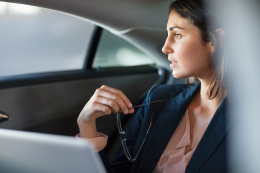 Pensive businesswoman with laptop in back seat of car - gettyimageskorea