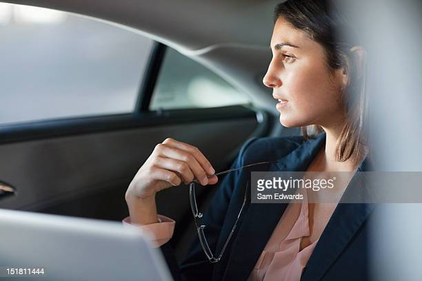 Pensive businesswoman with laptop in back seat of car