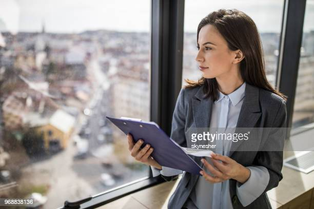 pensive businesswoman working on paperwork by the window. - clipboard stock pictures, royalty-free photos & images