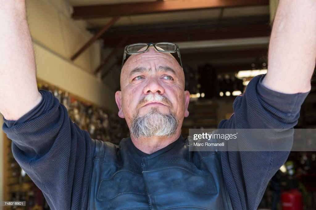 Pensive Caucasian man with arms raised : Stock Photo