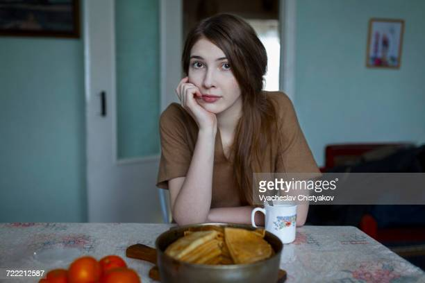 pensive caucasian woman sitting at table - kin in de hand stockfoto's en -beelden