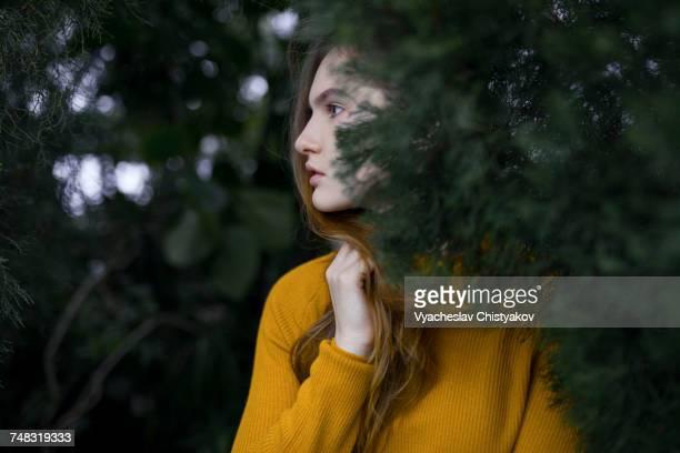 Pensive Caucasian woman standing near tree branch