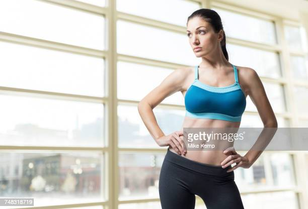 Pensive Caucasian woman standing with hands on hips