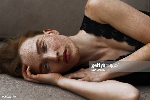 pensive caucasian woman with freckles laying on floor - sarda - fotografias e filmes do acervo