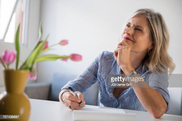 pensive caucasian woman writing on notepad - answering stock pictures, royalty-free photos & images