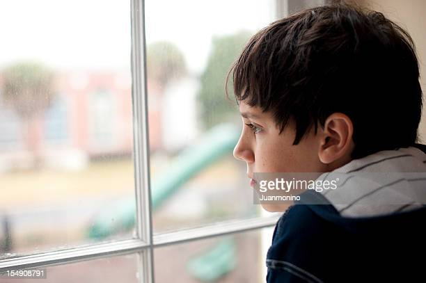 pensive child looking through a window - orphan stock pictures, royalty-free photos & images