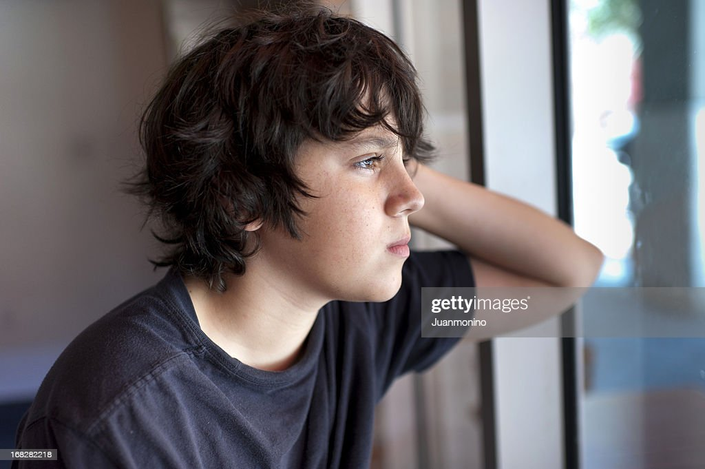 Pensive child looking through a window : Stock Photo