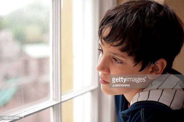 Pensive child looking through a window