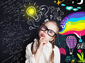 Pensive child school student with yellow lightbulb and school and childhood supplies design elements. Child ideas and development concept