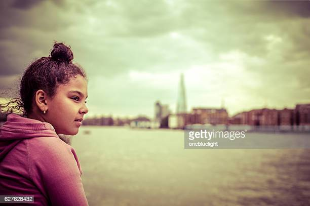 people: pensive child (9-10) sitting on river bank - london - onebluelight stock pictures, royalty-free photos & images