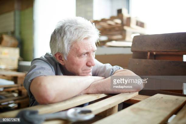 Pensive dreamy senior worker leaning on wooden trap
