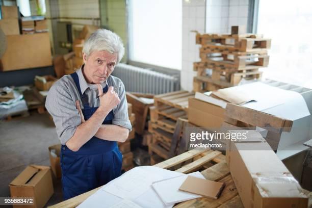 Pensive engineer in messy warehouse